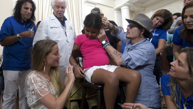 American actor Johnny Depp, right, puts a hearing device in the ear of a child while his wife, the actress Amber Heard, left, puts a bracelet on her arm, in Rio de Janeiro, Brazil, Thursday, Sept. 24, 2015. Starkey Hearing Foundation and the Hollywood Vampires band are joining forces in Rio de Janeiro to provide more than 200 children and adults in need the gift of hearing in advance of the supergroup's performance on the main stage at the Brazilian edition of Rock in Rio festival. (AP Photo/Silvia Izquierdo)
