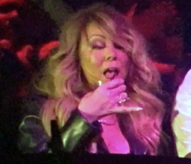 Mariah Carey shows off her curvy body to the crowd inside 1OAK in Las Vegas while getting close to DJ and holding a beverage in hand
