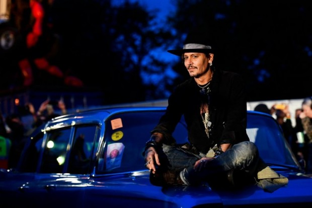Actor Johnny Depp poses on a Cadillac at Worthy Farm in Somerset during the Glastonbury Festival