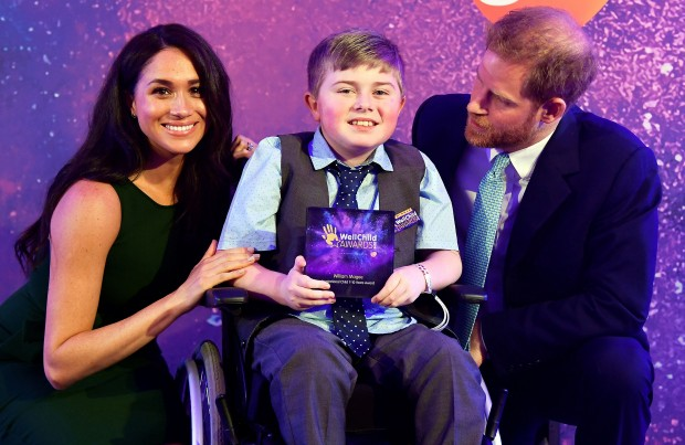 Britain's Prince Harry, Duke of Sussex, and Britain's Meghan, Duchess of Sussex pose for a photograph with award winner William Magee during the annual WellChild Awards in London on October 15, 2019. - WellChild is the national charity for seriously ill children and their families. The WellChild Awards celebrate the inspiring qualities of some of the country's seriously ill young people and the dedication of those who care for and support them. (Photo by TOBY MELVILLE / POOL / AFP) (Photo by TOBY MELVILLE/POOL/AFP via Getty Images)