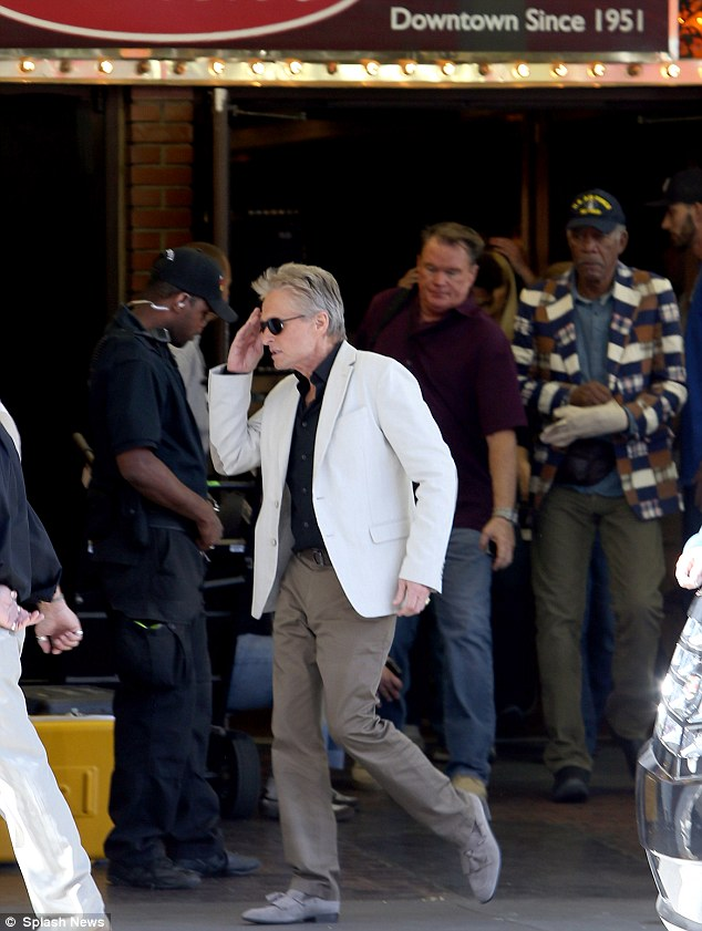 Marching salute: Michael Douglas put his hand to his head as he walked past Morgan Freeman on the set of Last Vegas