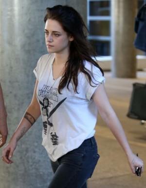 Kristen Stewart at LAX -  new fish tattoo or pens on a plane?