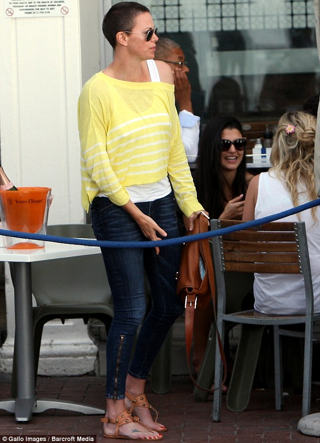 Not a natural blonde: Charlize Theron showed off her brunette buzz cut as she enjoyed lunch in Cape Town, South Africa