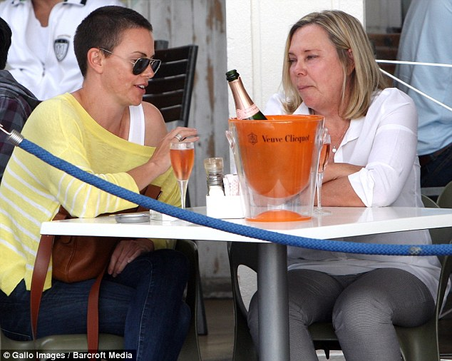 Mother-daughter time: Charlize looked happy and relaxed as she shared a bottle of rose champagne with her mother, Gerda